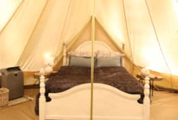 Queen bed in deluxe bell tent- air conditioner to the left