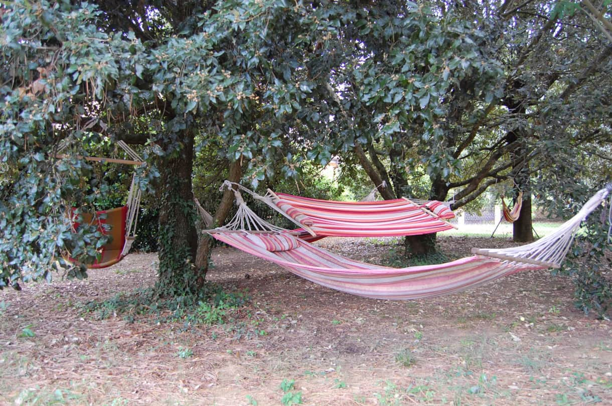 Lazy afternoons in the shaded hammocks next to the wood oven and pool-house of this Tuscan villa