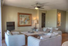 The spacious living room has seating for many with a large flat screen smart TV with internet access