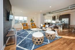Natural light pours into the spacious living room in Unit 4 with 2 chic armchairs and a cozy couch.