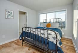 The 3rd bedroom in Unit 4 includes a plush queen-size bed and a closet.