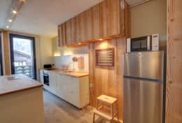 A spacious kitchen area with fridge, microwave, oven, toaster, kettle and utensils